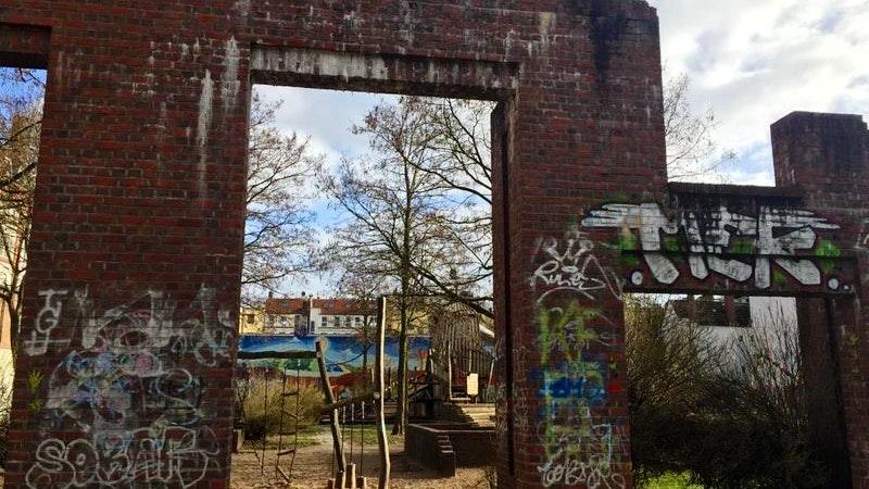 Auf dem Geisterspielplatz stehen noch Reste von roten Backsteinmauern, die mit Graffittis bemalt sind.