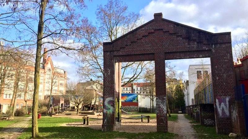 Tor zum Geisterspielplatz. Auf dem Bild sieht man ein Tor aus Backsteinen, das früher zu der Eingang zu einer Fabrikhalle war.