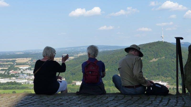 Freizeitverein Kreaktiv. Auf dem Foto sind drei ältere Menschen von hinten zu sehen, die auf einer Kante sitzend eine schöne Landschaft im Hintergrund betrachten.