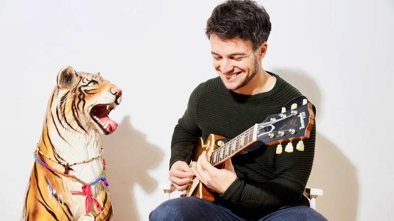 Sänger Simon sagt mit Gitarre und Tigerfigur