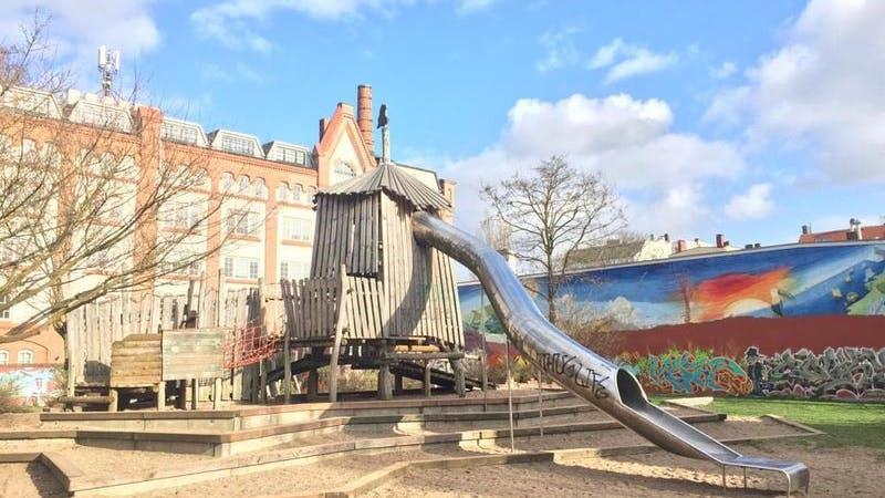Geisterspielplatz in Eimsbüttel. Auf dem Bild sieht man einen leeren Spielplatz mit einer Rutsche und einer bemalten Wand im Hintergrund.