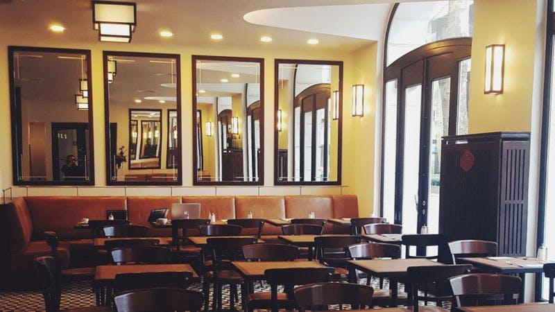 Das café des Artistes am Gerhart-Hauptmann-Platz. Auf dem Bild ist der Innenraum des Café zu sehen. Viele Stühle und Tische. An den Wänden hängen große Spiegel.