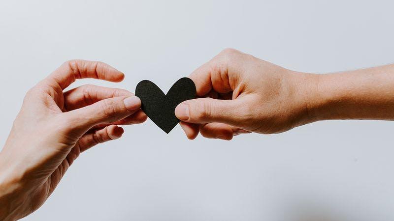 Zwei Personen, die zusammen ein Herz halten