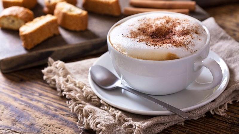 Tasse Cappuccino auf Holztisch
