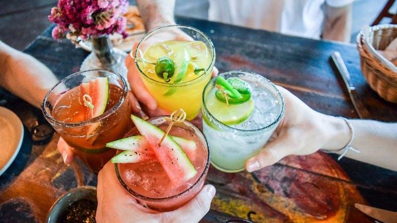 Freunde stossen mit bunten und fruchtigen Cocktails an