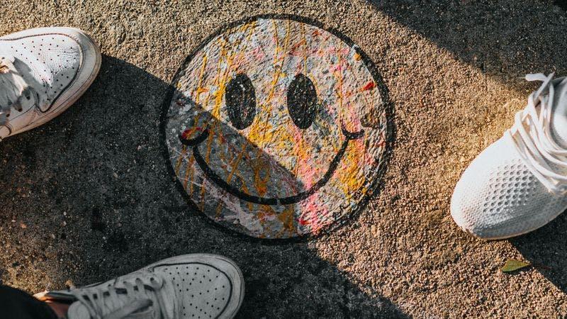 Menschen stehen um einen Smiley aus Kreide am Boden