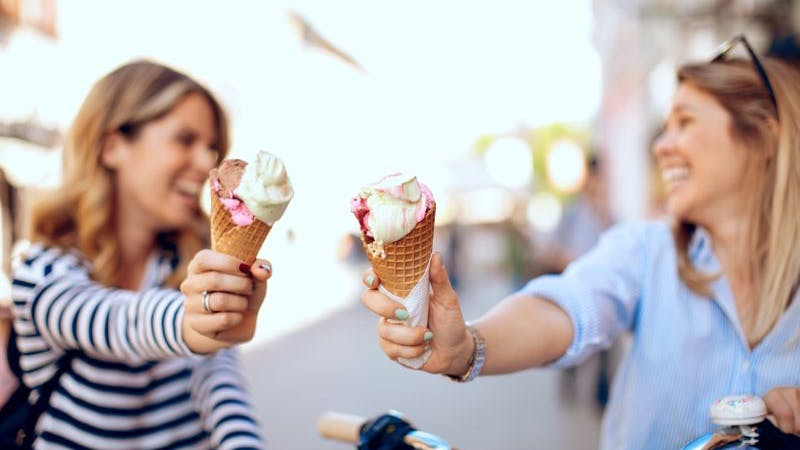Zwei Frauen halten Eiscreme in einer Stadt an einem sonnigen Tag.