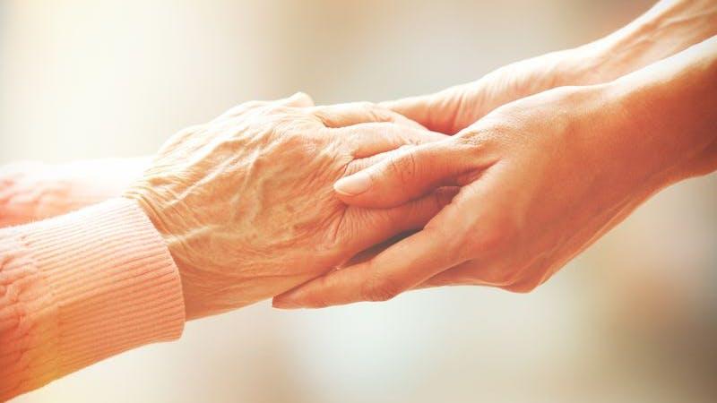 Alte und junge Hände liegen ineinander