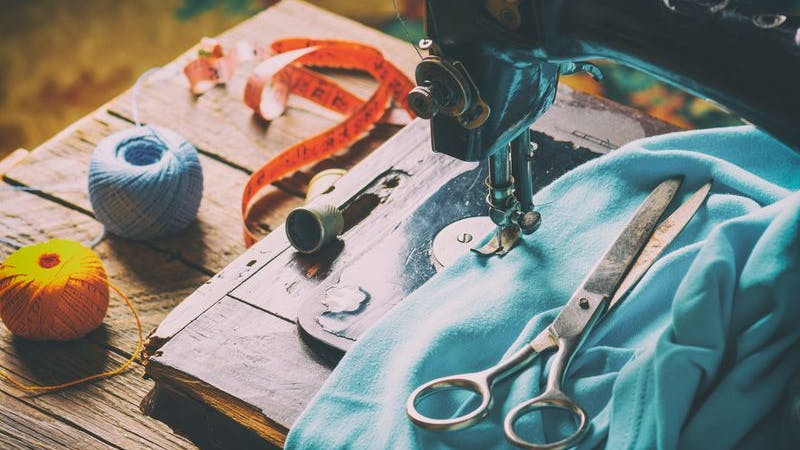Nähmaschine, Stoffe und Wolle auf Tisch