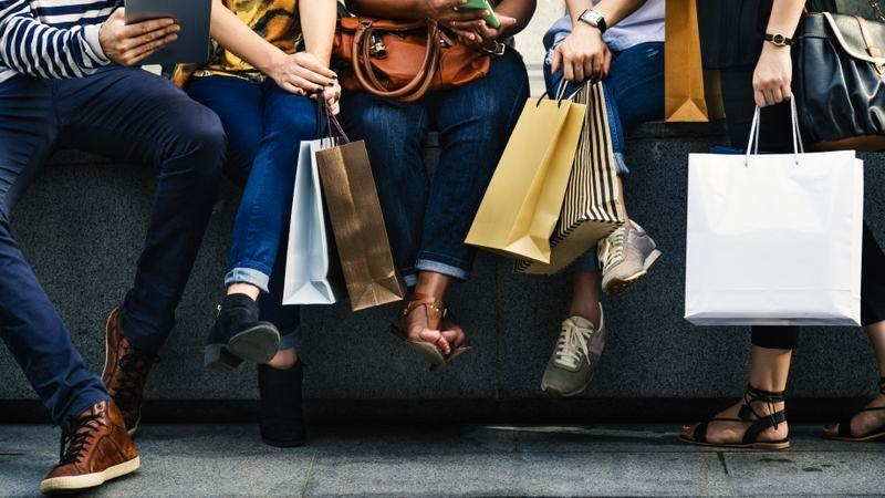 Menschen mit Einkaufstaschen sitzen auf Steinbank