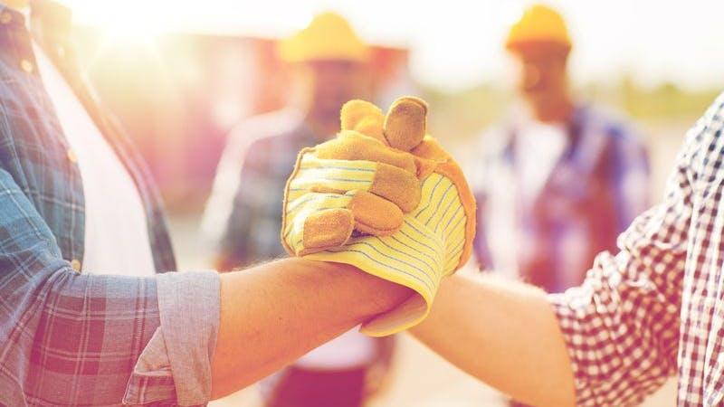 Hände in Bauarbeiterhandschuhen