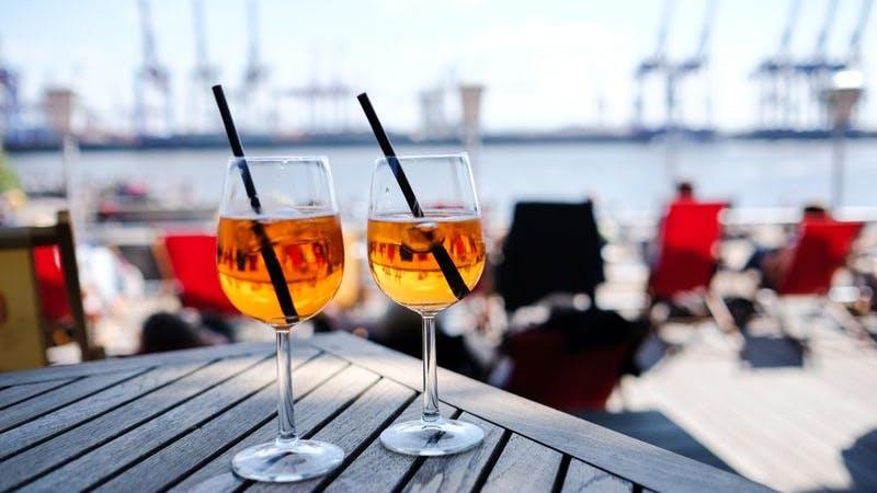 Zwei Gläser auf einem Tisch, im Hintergrund die Elbe