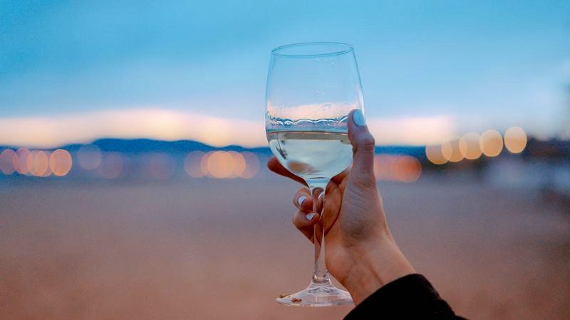 Glas Weißwein vor unscharfem Hintergrund