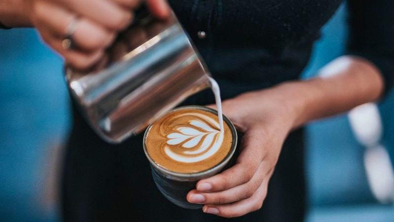 Café Petit. Auf dem Bild sieht man eine Person, die Milch in eine Kaffeetasse kippt.
