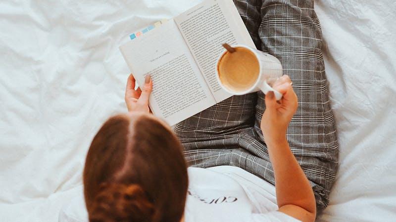 Frau liest ein Buch im Bett