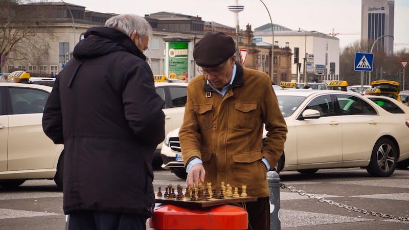 Männer spielen Schach auf Mülleimer