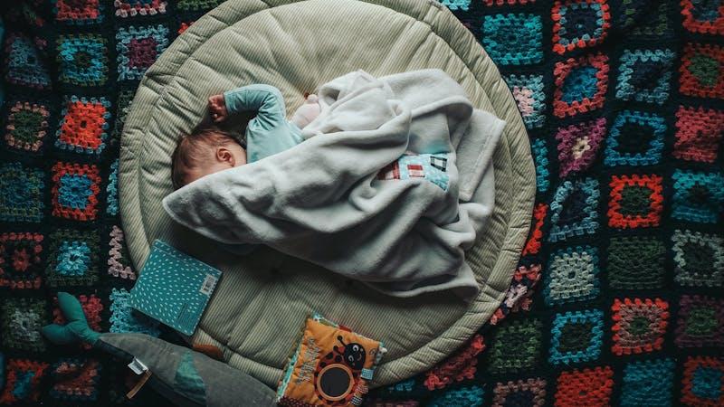 Baby liegt unter einer Decke